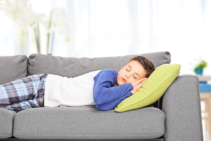 Cute little boy sleeping on sofa indoors