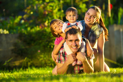 Happy young family having fun outdoors in summer. Mother, father and their cute little daughters are playing in the sunny garden. Happy parenthood and childhood concept. Focus on the father.