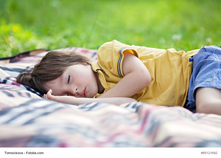 Cute little boy, sleeping on a picnic blanket, outdoors in a summer sunny afternoon
